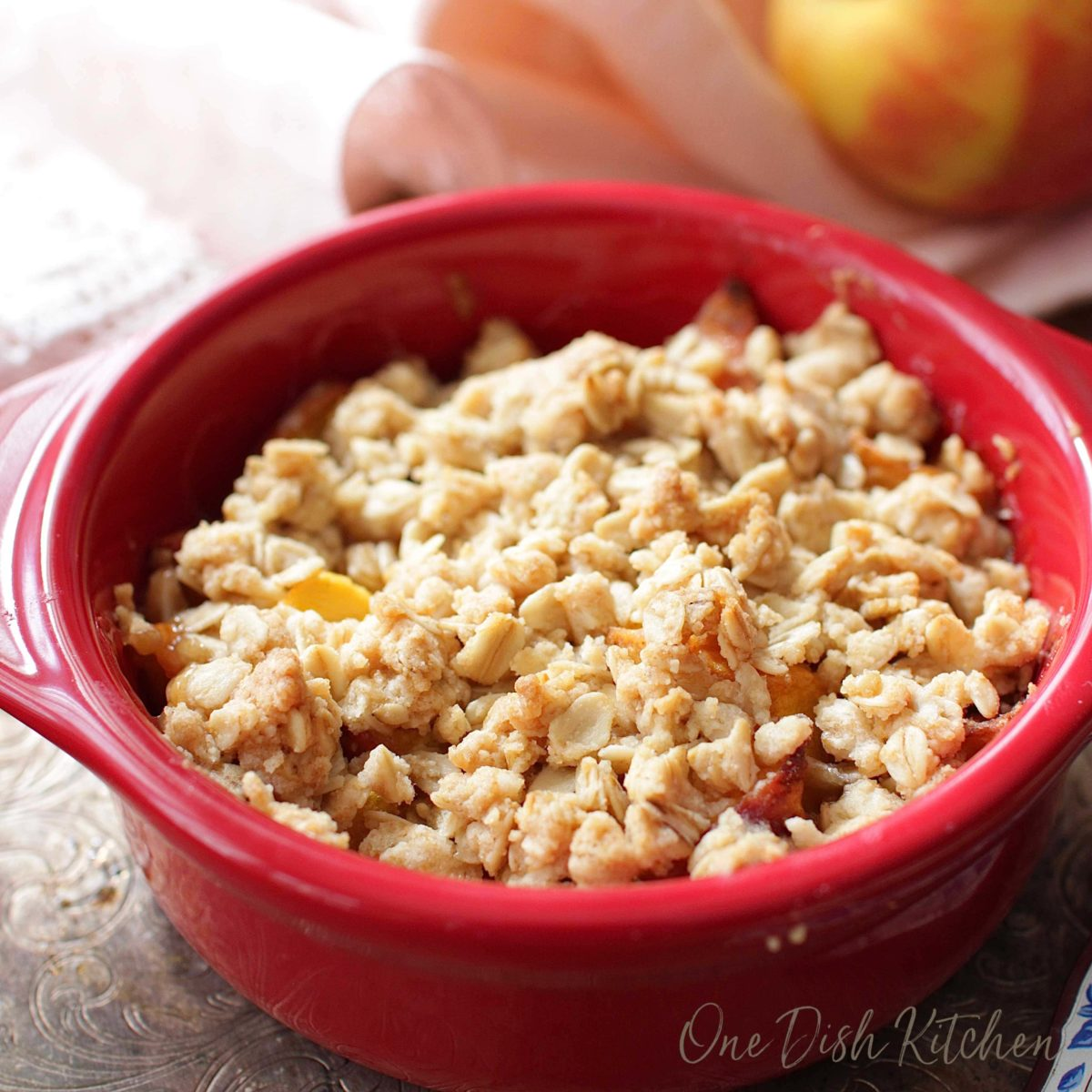 a peach crisp with an oatmeal topping in a red bowl on a tray.