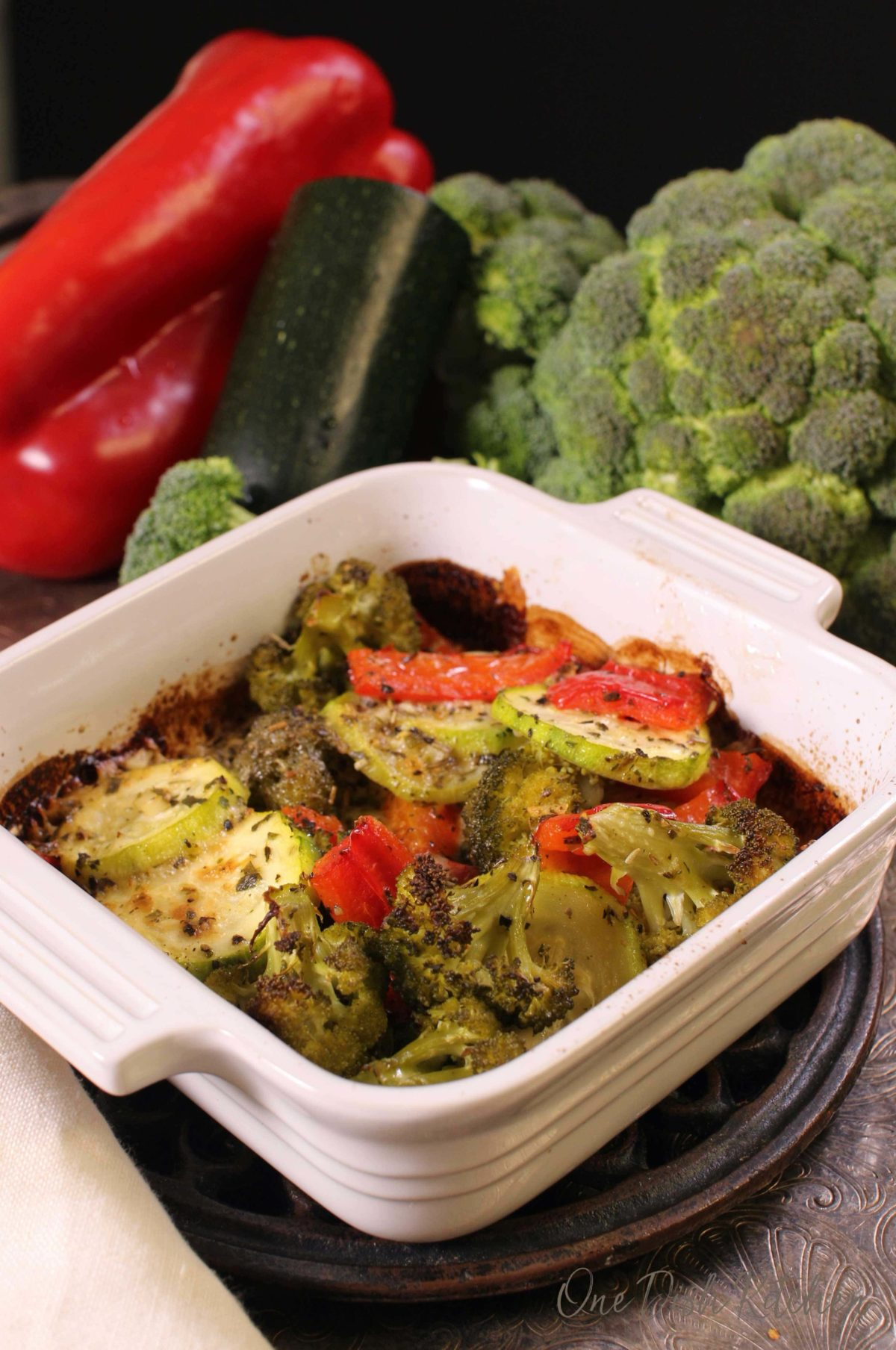 zucchini, red peppers, and onions cooked in a small baking dish with a cheese topping.
