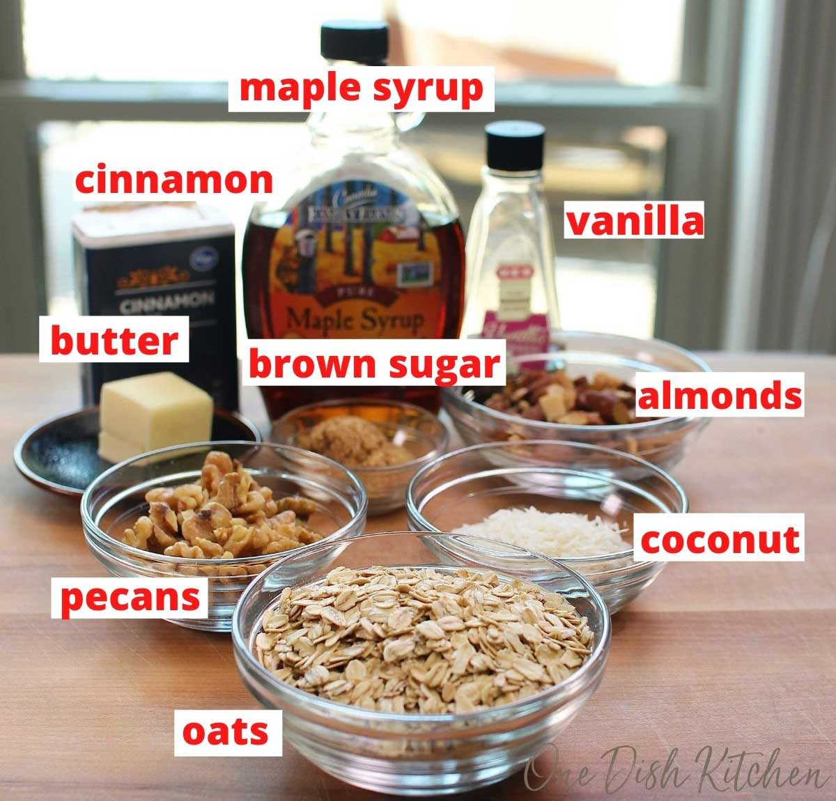 the ingredients needed to make butter pecan granola on a brown table next to an open window.