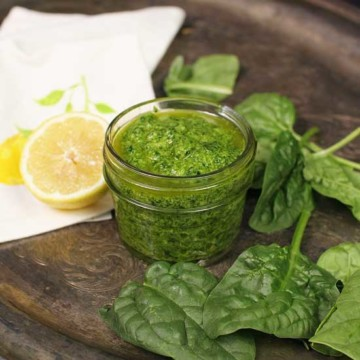 pesto in a small jar next to a half of a lemon.