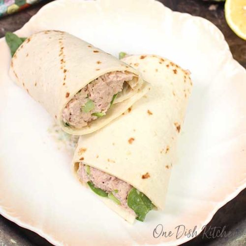 an overhead photo of a tuna wrap on a white plate with peach colored edges.