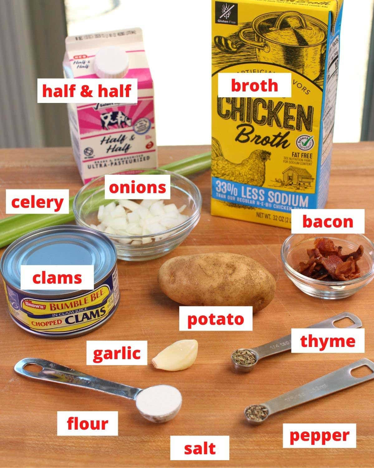 the ingredients needed in new england clam chowder on a brown table labeled.