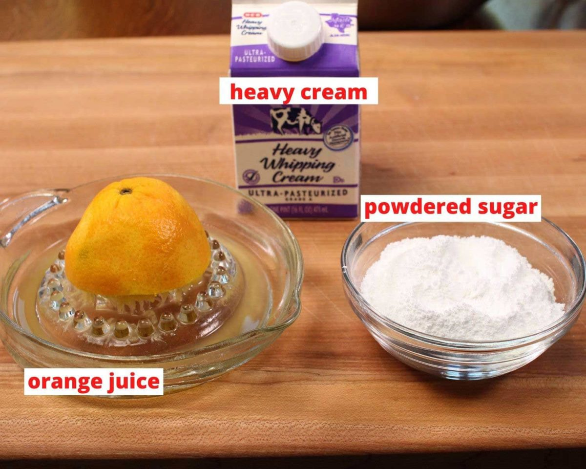 powdered sugar, orange juice, and cream on a brown table.