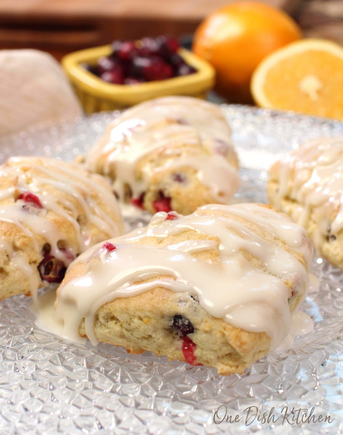 cranberry orange scones on a clear plate next to a bowl of fresh cranberries.