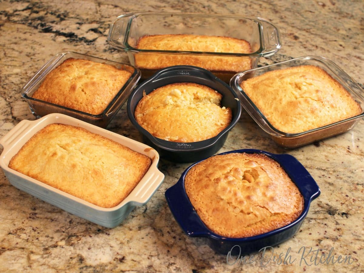6 cakes baked in different sized pans on a brown kitchen counter.