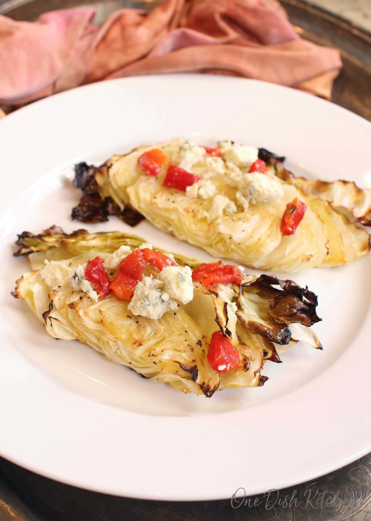 roasted cabbage topped with blue cheese and red peppers on a white plate next to an orange napkin