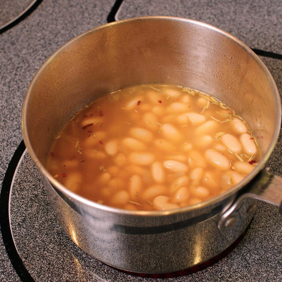 a pot of beans simmering in a broth