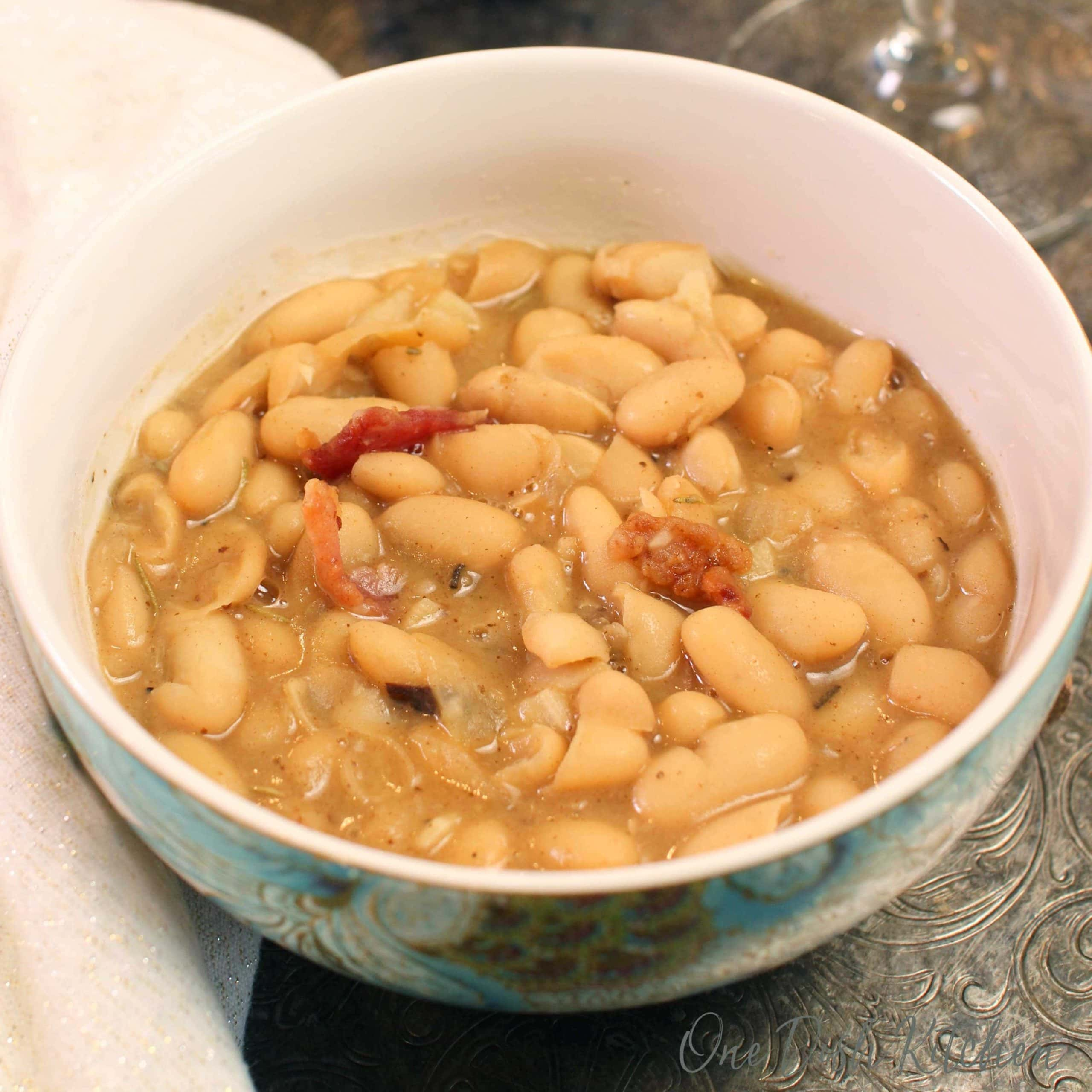 a bowl of white bean soup with bacon