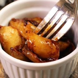 fried fried apples in a bowl next to a fork