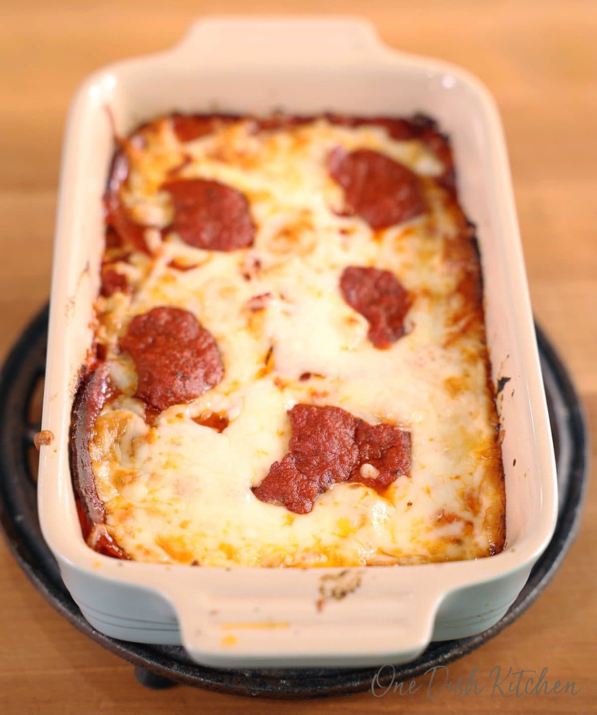 a small detroit style pizza in a blue rectangular baking dish