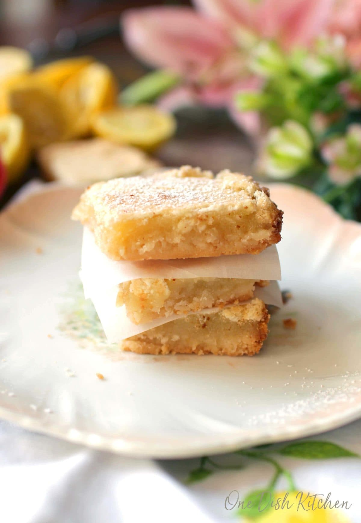 three lemon bars stacked on top of each other on a white plate next to lemon slices and flowers