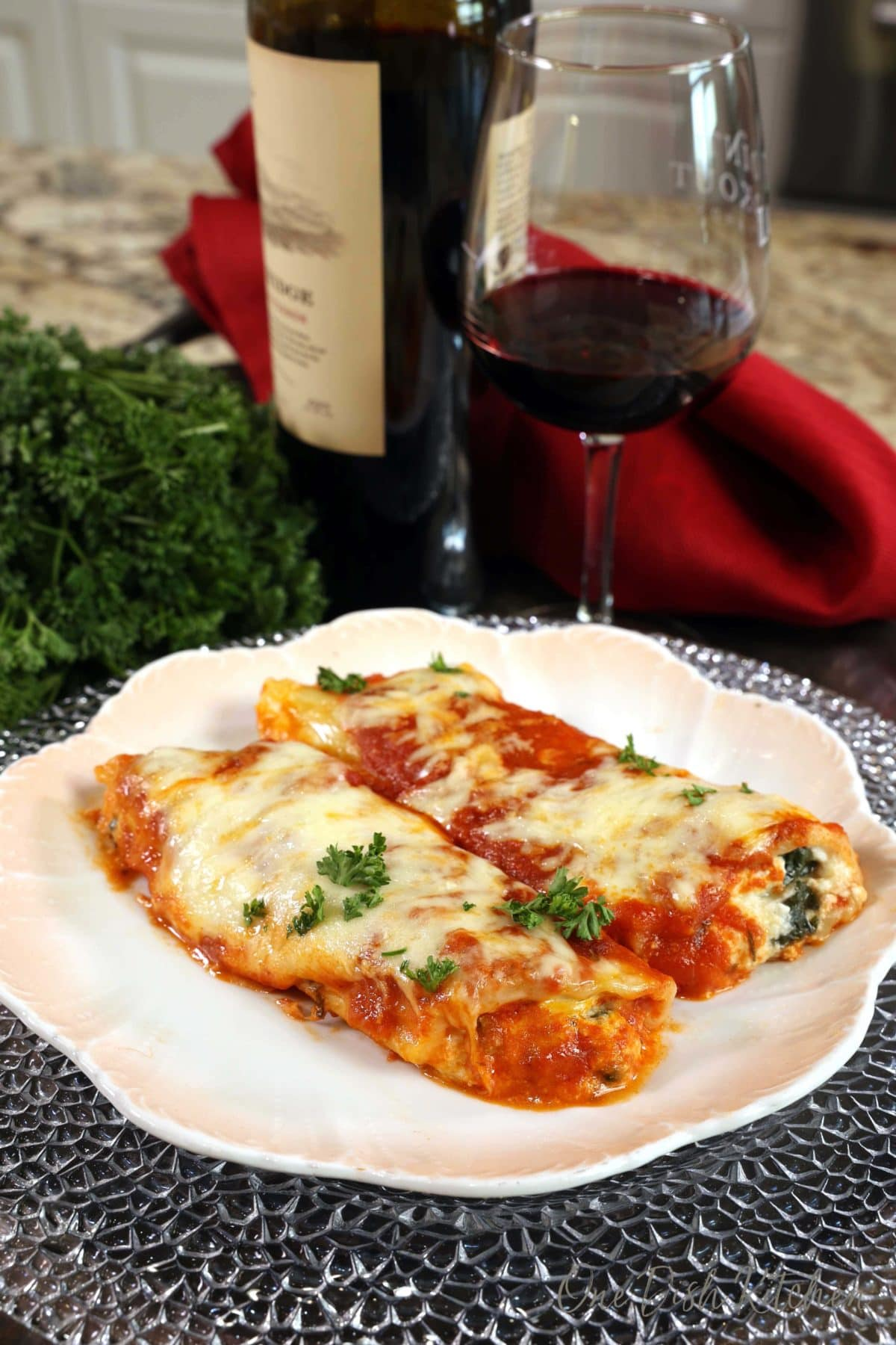 two stuffed manicotti shells on a white plate next to a bottle of red wine