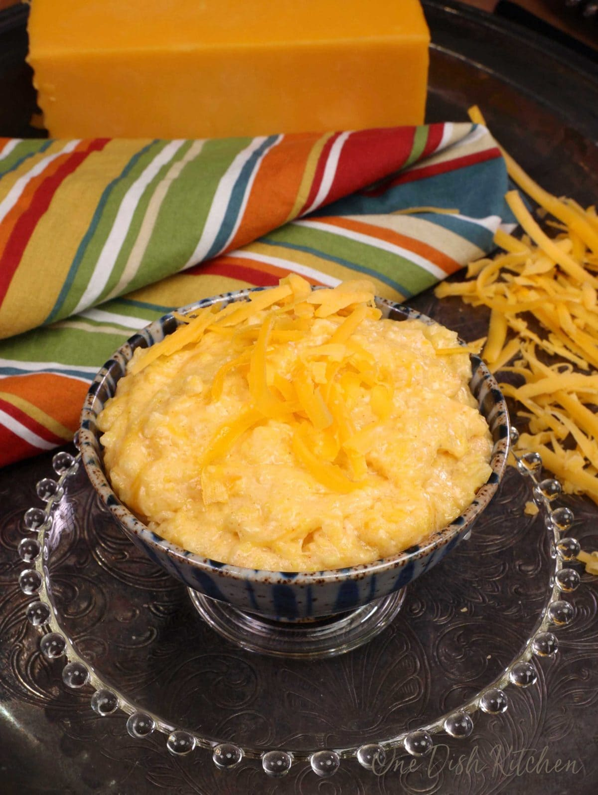 a small bowl of cheese grits next to shredded cheese and a large block of cheese in the background
