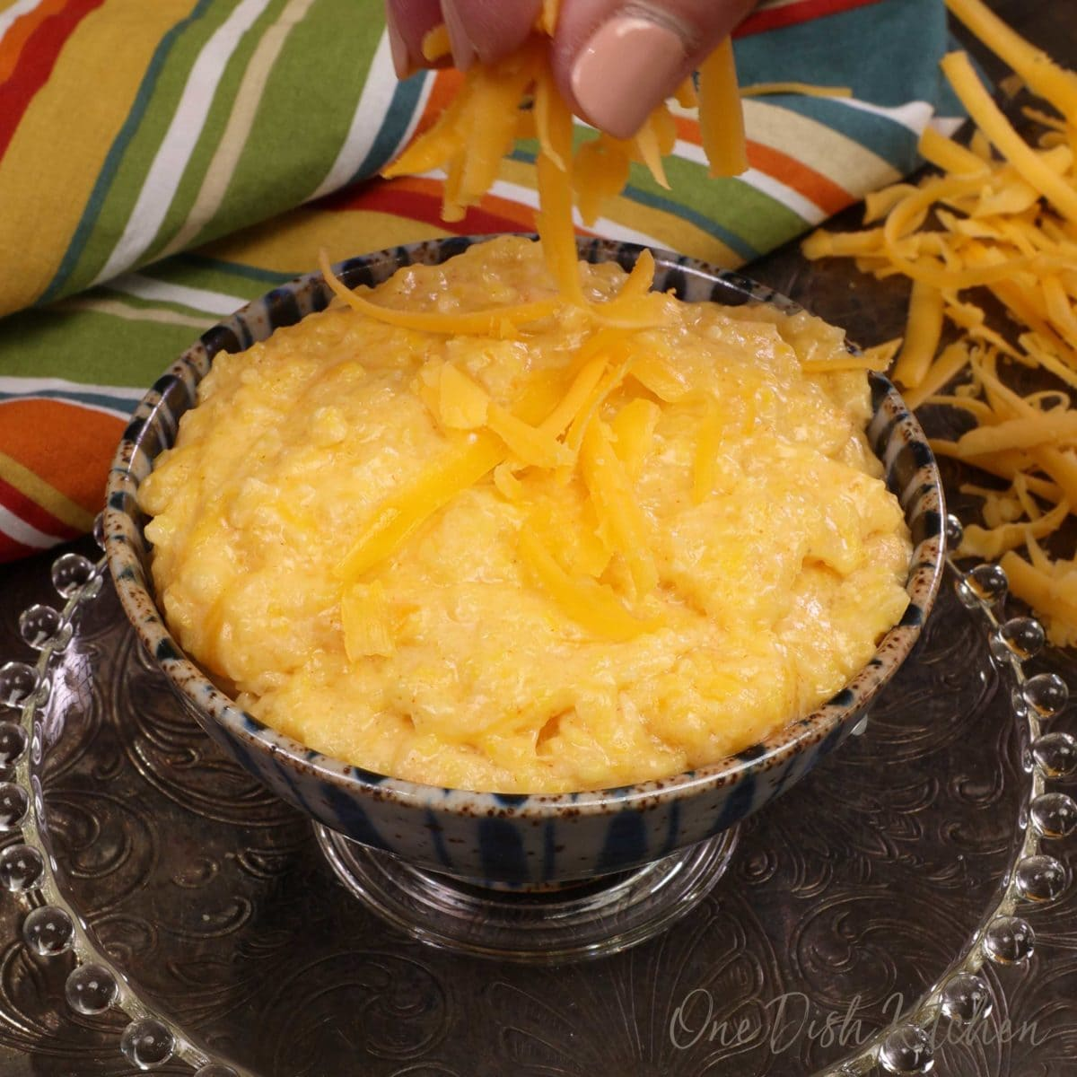 a small blue bowl filled with cheese grits with a hand sprinkling extra cheese over the top.
