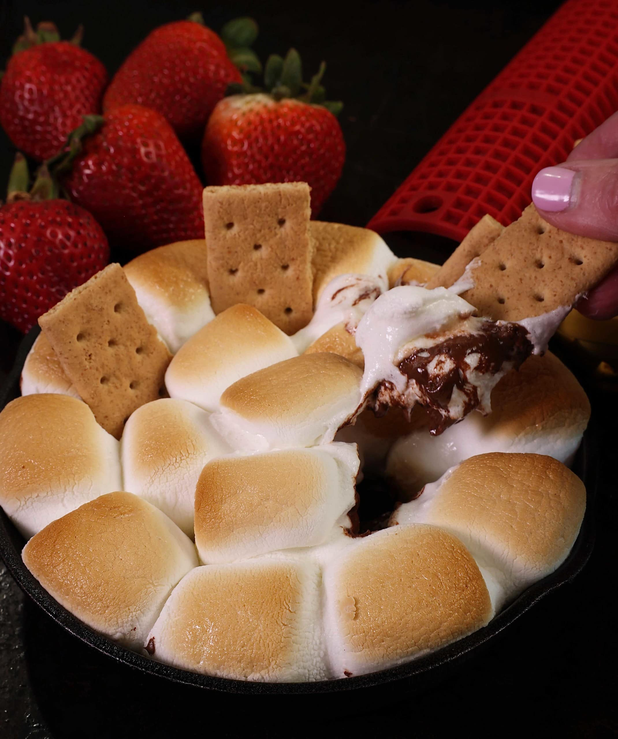 a graham cracker dipped into a skillet filled with melted chocolate and toasted marshmallows