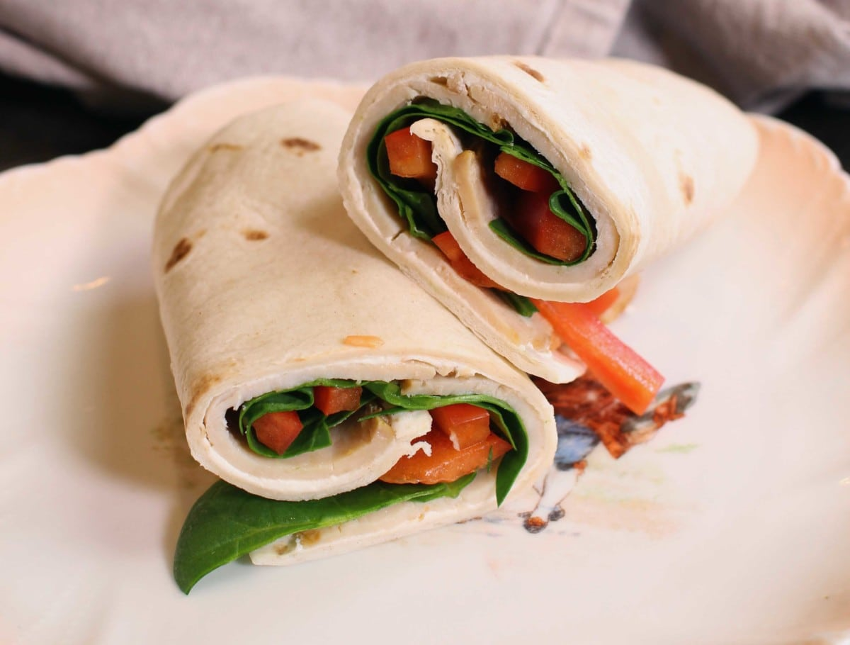 two pieces of a spinach and turkey wrap on a white plate.