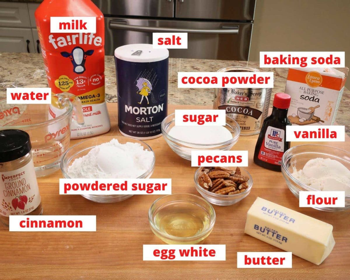 sugar, milk, cocoa, pecans, vanilla, egg whites, and other baking ingredients on a wooden cutting board.