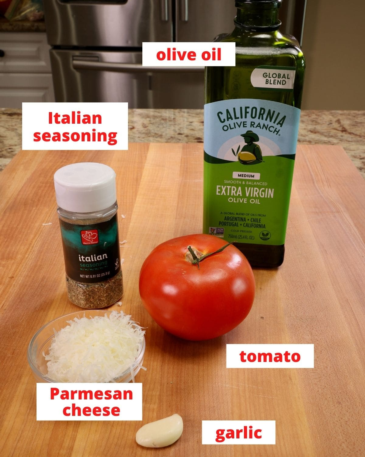 a tomato, olive oil, parmesan cheese, garlic, and italian seasoning on a wooden cutting board in a kitchen