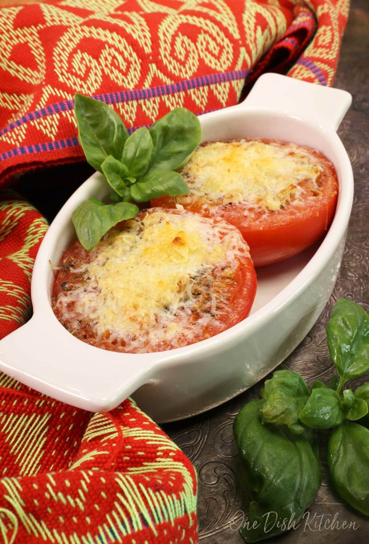 two broiled tomatoes in a white oval dish topped with melted parmesan cheese and fresh basil