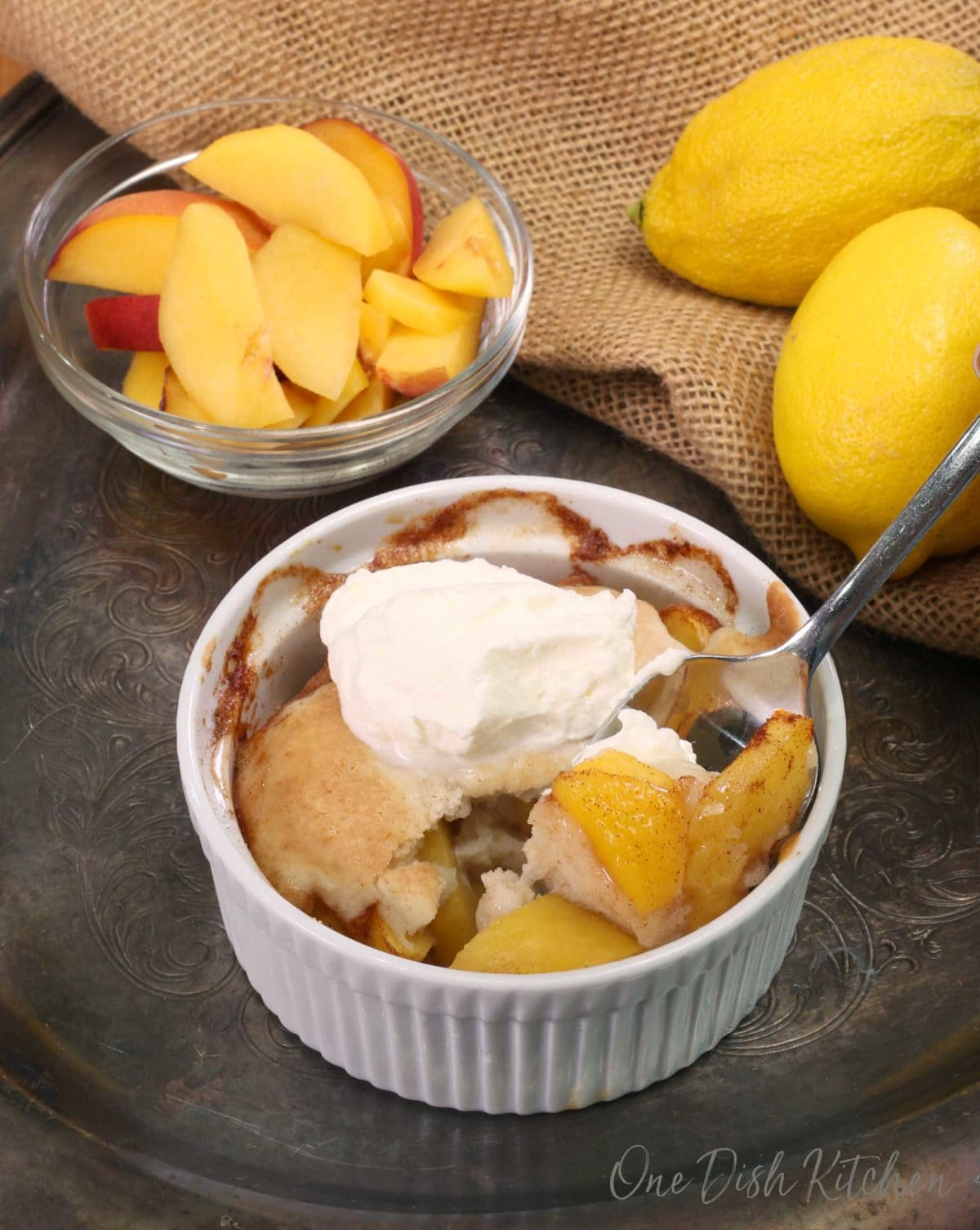 a spoonful of peaches from a peach cobbler with the cobbler in the background
