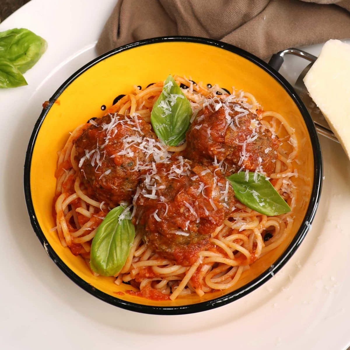a yellow bowl filled with spaghetti and meatballs next to a wedge of fresh parmesan cheese and a brown napkin