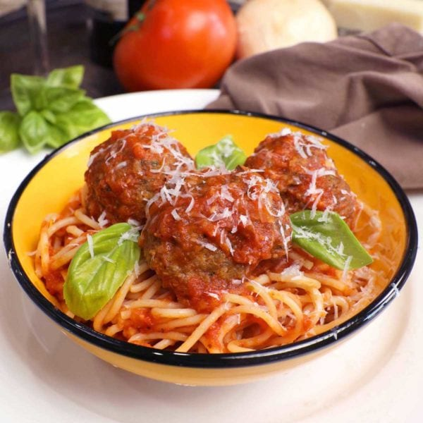 a bowl of spaghetti topped with three meatballs and fresh basil on a white plate next to a bottle of red wine