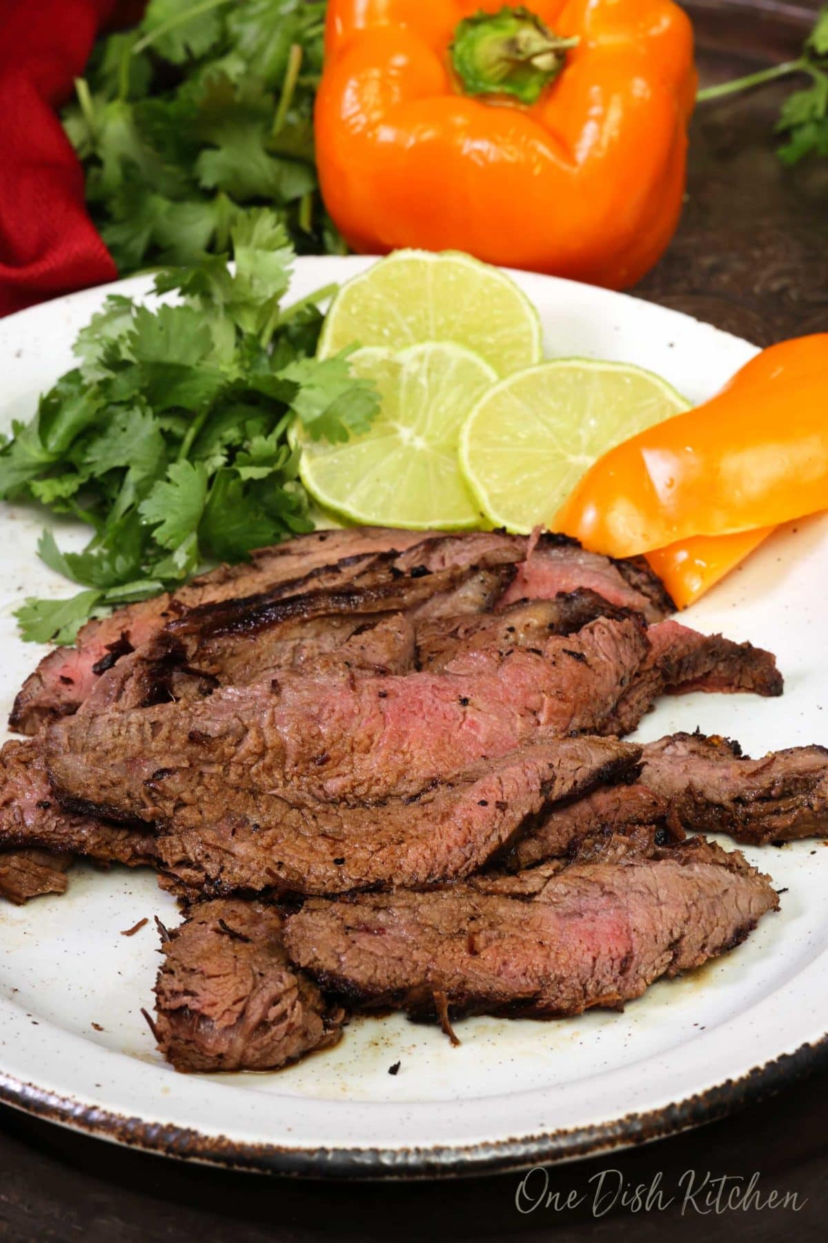 carne asada on a white plate next to cilantro, lime slices, and sliced peppers