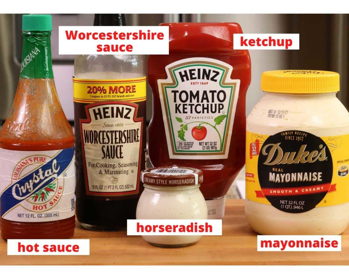 russian dressing ingredients on a wooden cutting board: ketchup, mayonnaise, hot sauce, horseradish, and worcestershire sauce
