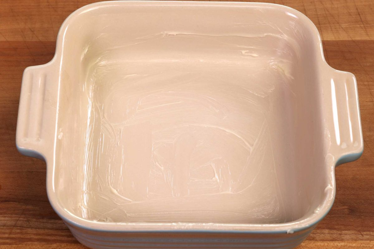 a small square buttered baking dish on a brown table