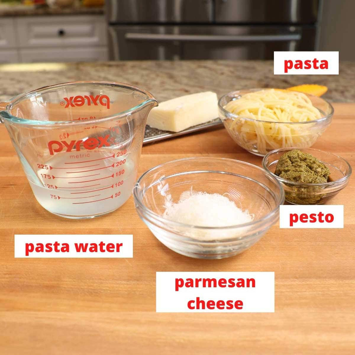 pasta, parmesan cheese,pesto and pasta water on a brown wooden cutting board