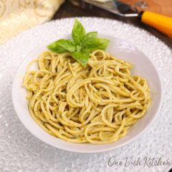 a white bowl filled with pesto pasta with a wedge of parmesan on the side of the table