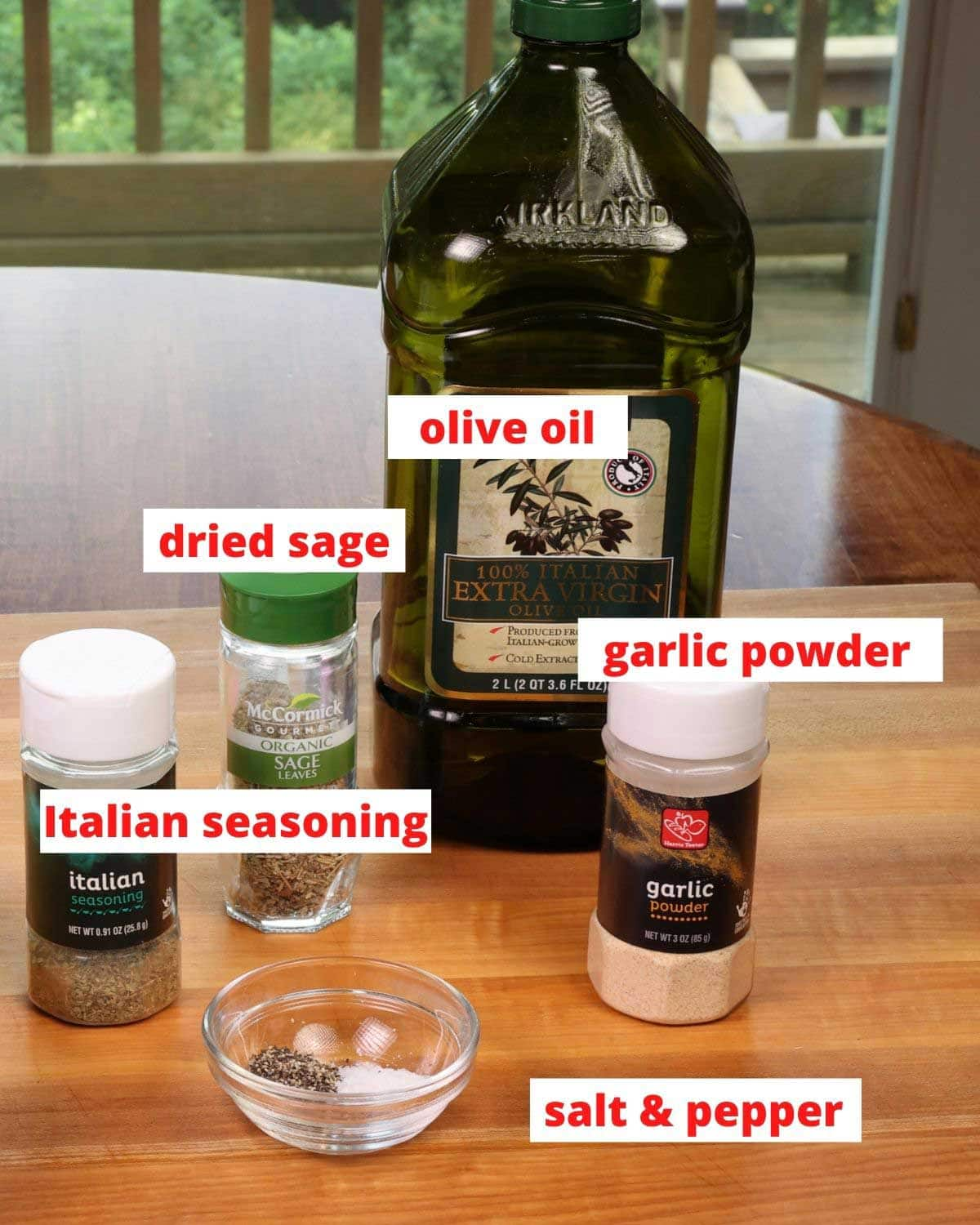 seasonings and olive oil on a wooden cutting board in a kitchen
